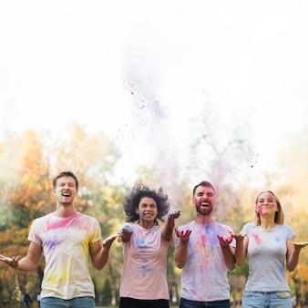 Plano medio de amigos arrojando pintura para holi