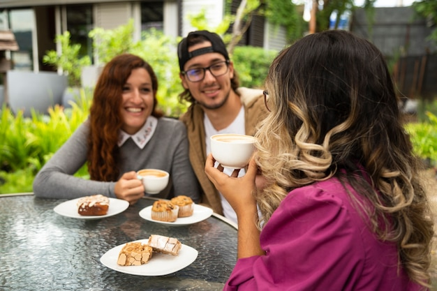 Plano medio de amigos disfrutando de un café