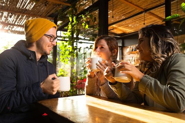 Plano medio de amigos en la terraza del café
