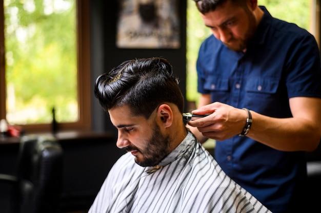 Plano medio de barbero que le da al cliente un nuevo peinado