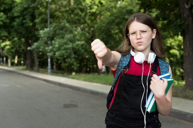 Plano medio de una chica de secundaria decepcionada sosteniendo libros en las manos
