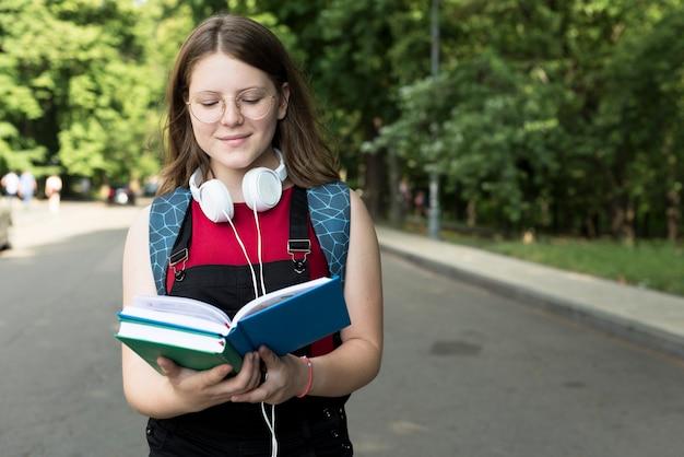Plano medio de una chica de secundaria leyendo un libro