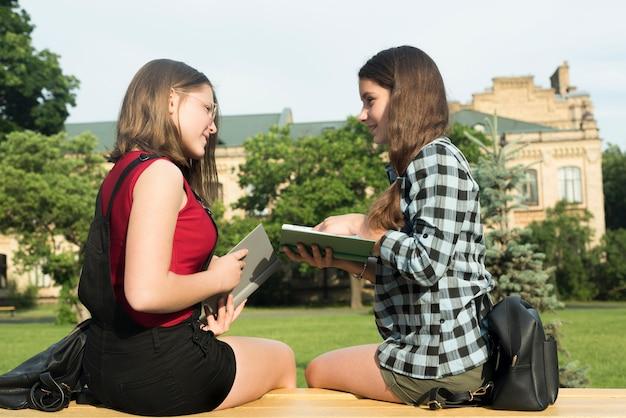 Plano medio de dos chicas de secundaria estudiando