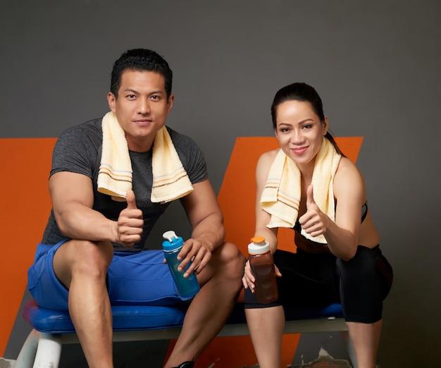 Plano medio de dos entrenadores que muestran los pulgares hacia la cámara para apoyar y motivar a hacer deporte