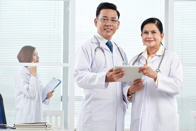 Plano medio de dos médicos de pie en el consultorio médico discutiendo un caso clínico