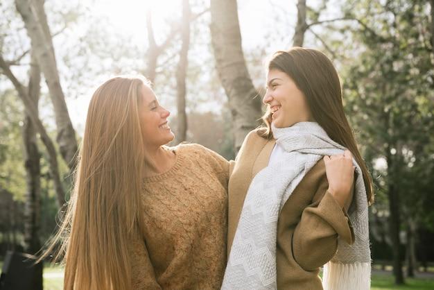 Plano medio de dos mujeres hablando en el parque.