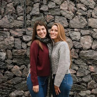 Plano medio de dos mujeres sonrientes frente a un muro de piedra