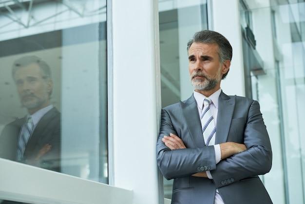 Plano medio del empresario de pie con los brazos cruzados apoyándose en el marco de la ventana