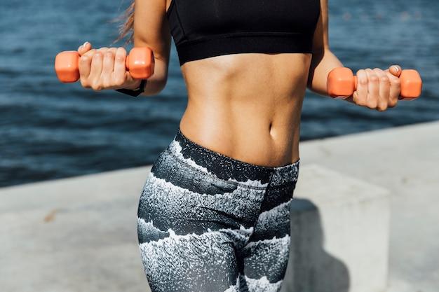 Plano medio de entrenamiento con pesas mujer
