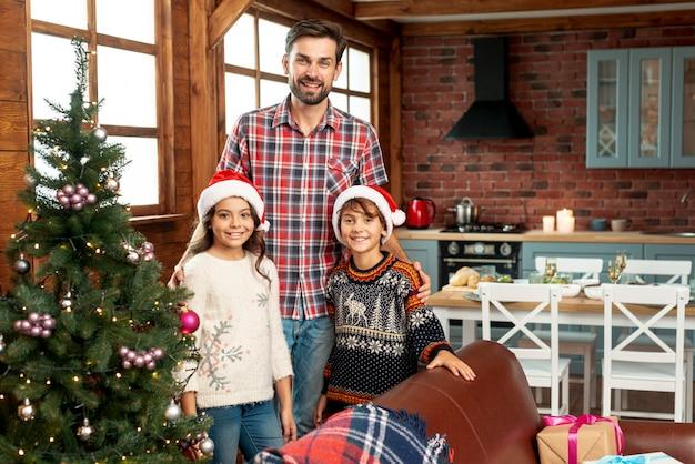 Plano medio familia feliz posando cerca del árbol de navidad