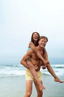 Plano medio feliz hombre y mujer en la playa