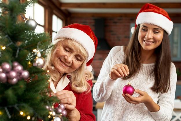 Plano medio feliz madre e hija decorando el árbol de navidad