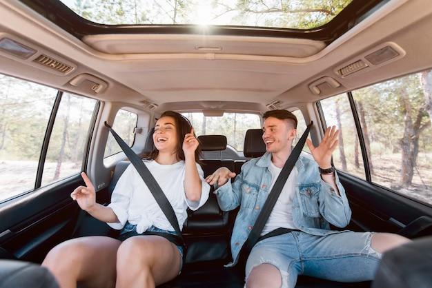 Plano medio feliz pareja bailando dentro del coche