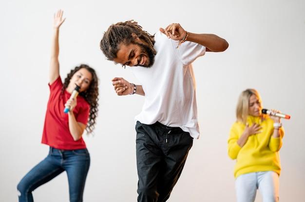 Plano medio, gente multirracial cantando y bailando
