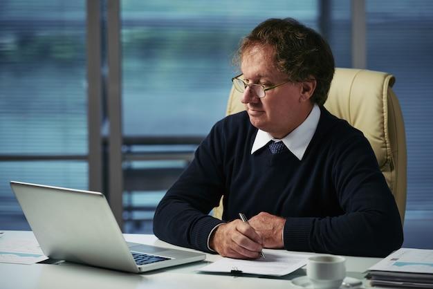 Plano medio del gerente de negocios que prepara el informe para la junta ejecutiva