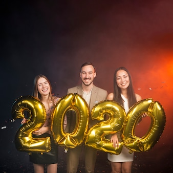 Plano medio del grupo de amigos con globos en la fiesta