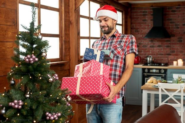 Plano medio hombre feliz llevando regalos