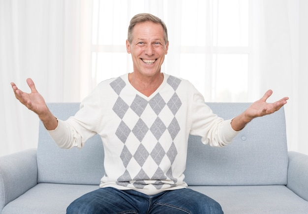 Plano medio hombre feliz sentado en el sofá