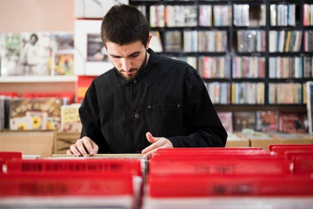 Plano medio de un hombre joven en busca de vinilos en la tienda.