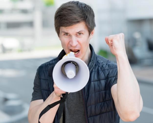 Plano medio del hombre con megáfono protestando en la calle