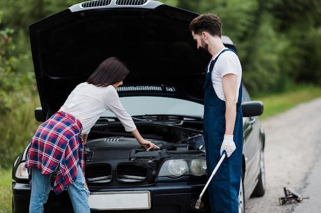 Plano medio del hombre y la mujer comprobando el motor