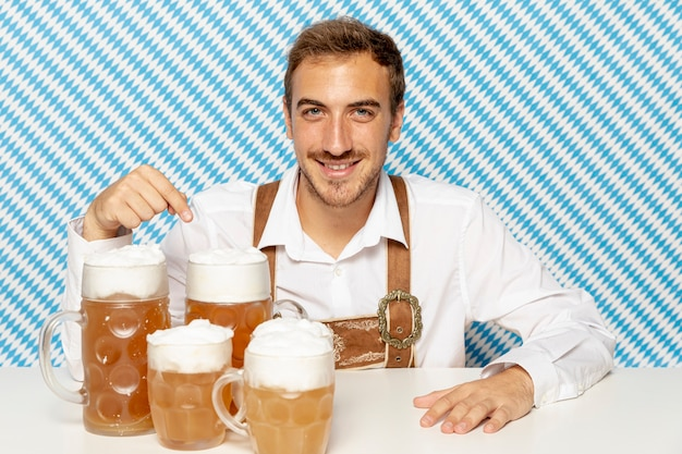 Plano medio del hombre con pintas de cerveza rubia