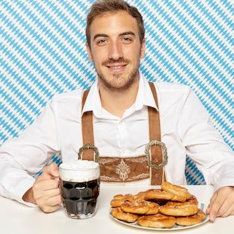 Plano medio del hombre con pretzels suaves y cerveza negra