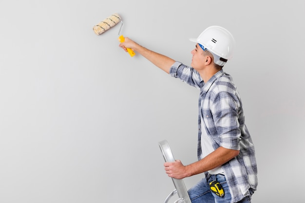 Plano medio del hombre que sostiene un rodillo de pintura con espacio de copia
