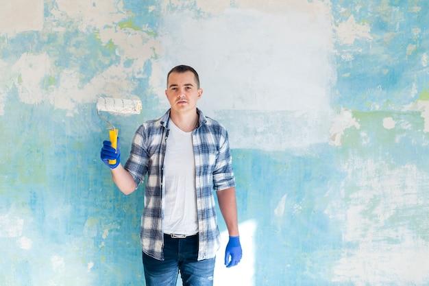 Plano medio del hombre que sostiene un rodillo de pintura