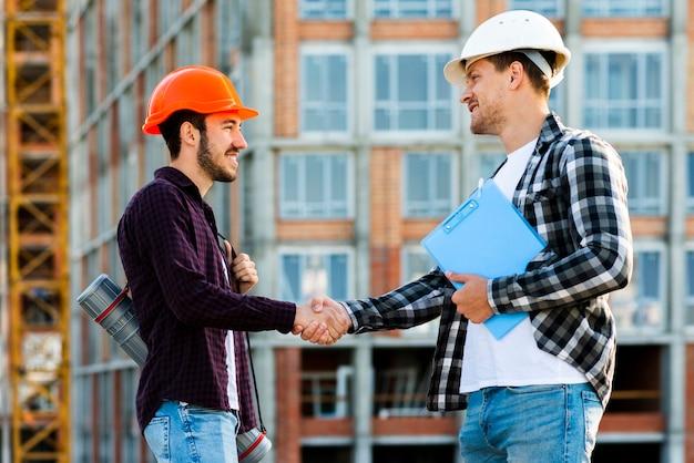 Plano medio del ingeniero y arquitecto dándose la mano.
