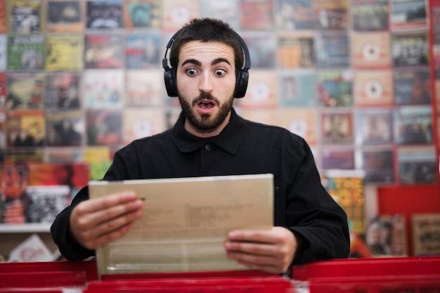 Plano medio de un joven escuchando música en una tienda de vinilos.