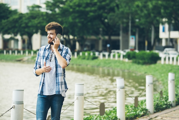 Plano medio del joven haciendo una llamada telefónica de pie en la orilla del estanque