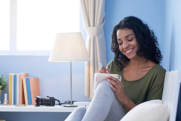 Plano medio de la joven haciendo notas casualmente descansando en el sofá de su habitación