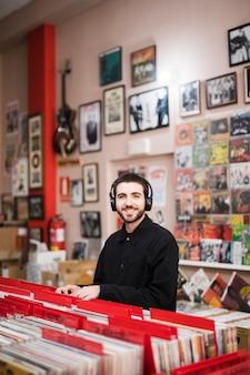 Plano medio del joven mirando a la cámara en una tienda de vinilo