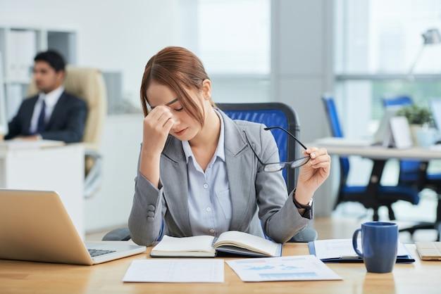 Plano medio de la joven mujer asiática sentada en el escritorio en la oficina y frotándose la nariz