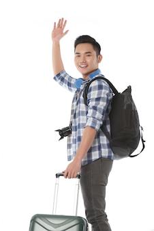 Plano medio de un joven turista que se despide mientras se va de viaje