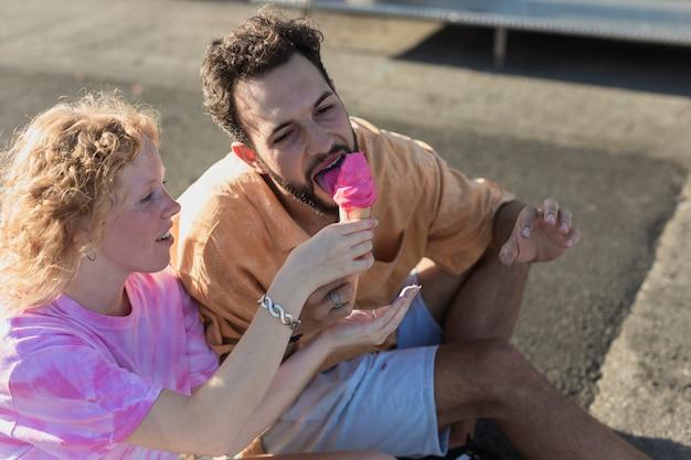 Plano medio linda pareja con helado de rosa