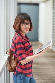 Plano medio de un lindo estudiante asiático revisando material para la clase