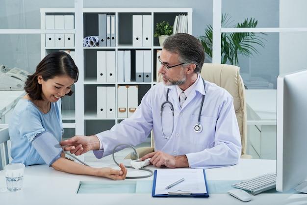 Plano medio del médico que controla la presión arterial del paciente femenino