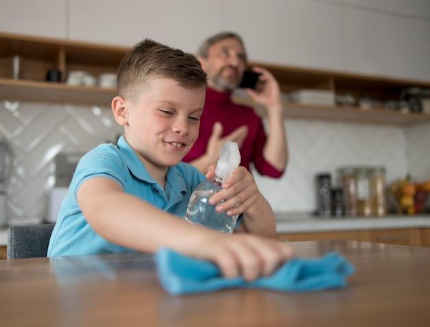 Plano medio de mesa de limpieza de niño sonriente