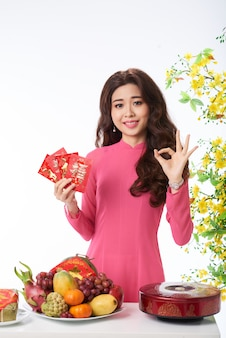 Plano medio de una mujer asiática felicitando el festival de primavera con un gesto
