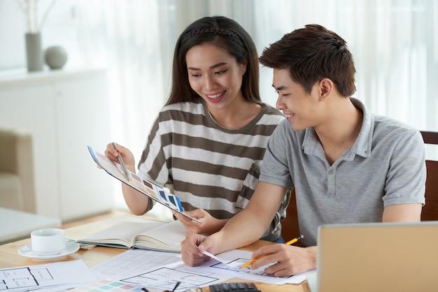 Plano medio de una mujer asiática que comparte ideas creativas sobre el diseño del hogar con su esposo
