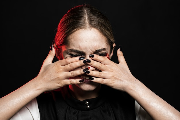 Plano medio de mujer cubriéndose la cara