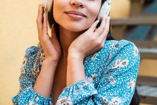 Plano medio de mujer escuchando música
