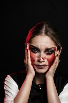 Plano medio de mujer con maquillaje ensangrentado