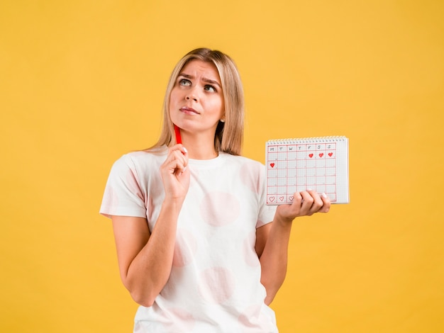 Plano medio de mujer pensando y sosteniendo el calendario del período