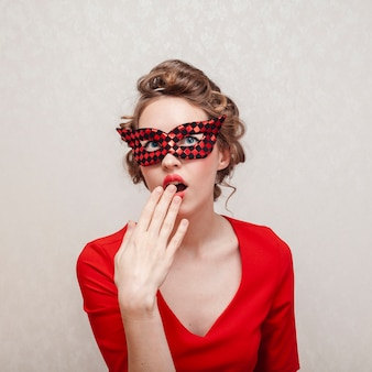 Plano medio de la mujer que cubre su rostro con máscara de carnaval