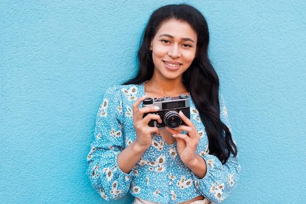 Plano medio de mujer sosteniendo una cámara vintage