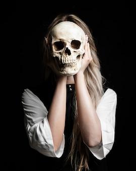 Plano medio de mujer sosteniendo cráneo humano