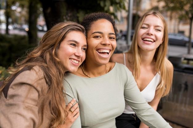 Plano medio de mujeres riendo tomando un selfie
